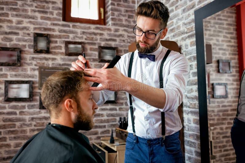 O cabeleireiro ajusta o cabelo um cliente com um pente imagem de stock royalty free