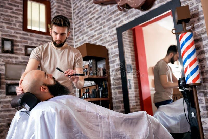 O cabeleireiro barbeia a barba do ` s do homem imagem de stock