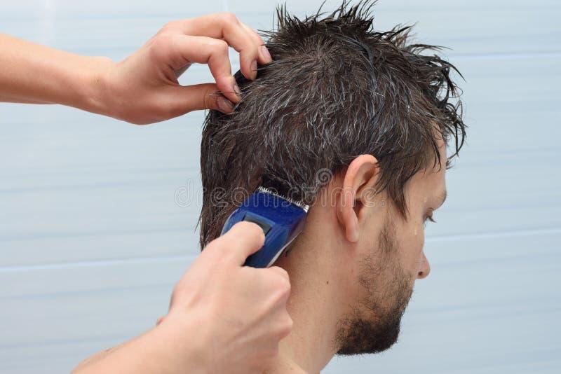 O cabeleireiro começa a cortar o cabelo na cabeça do homem em casa imagens de stock