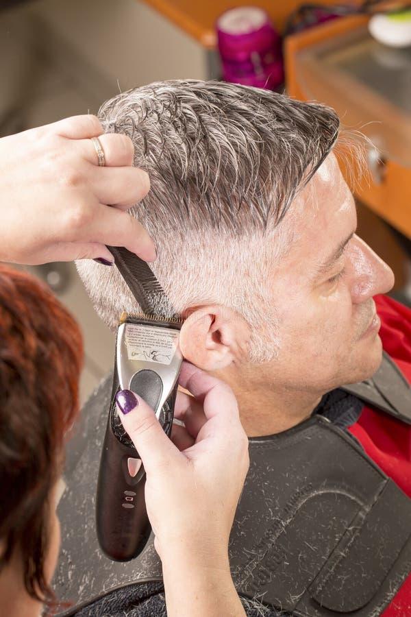 O cabeleireiro corta o cabelo fotografia de stock royalty free
