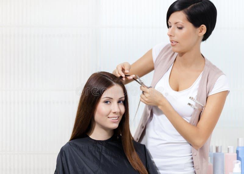 O cabeleireiro corta o cabelo da mulher no cabeleireiro fotos de stock royalty free