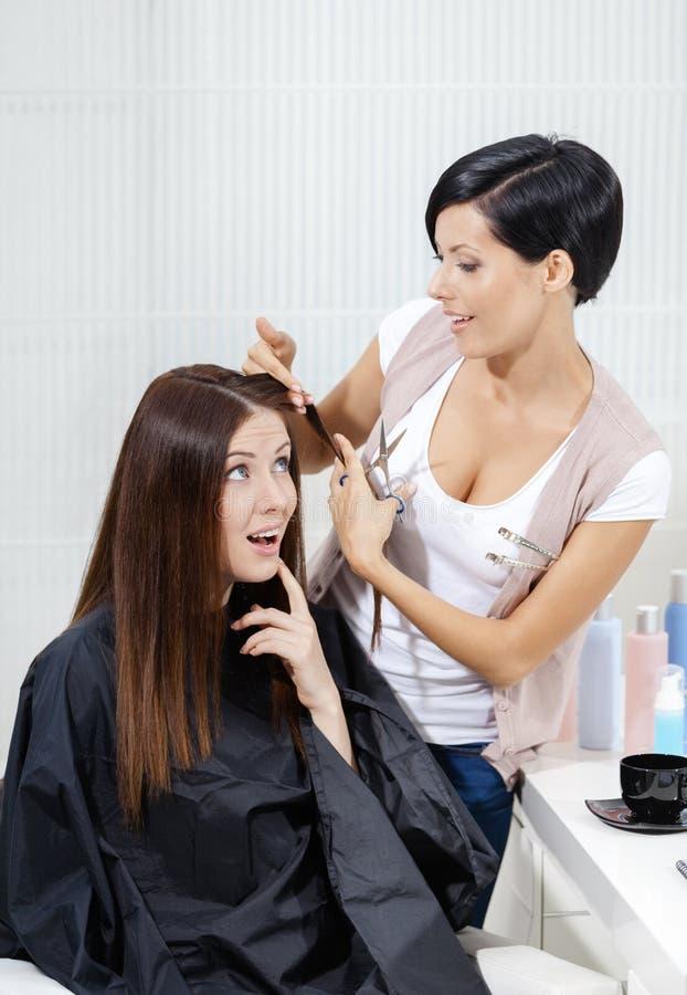 O cabeleireiro corta o cabelo da mulher no salão de beleza do cabeleireiro foto de stock royalty free