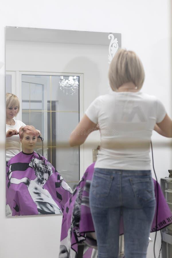 O cabeleireiro da mulher faz o penteado em um sal?o de beleza imagem de stock
