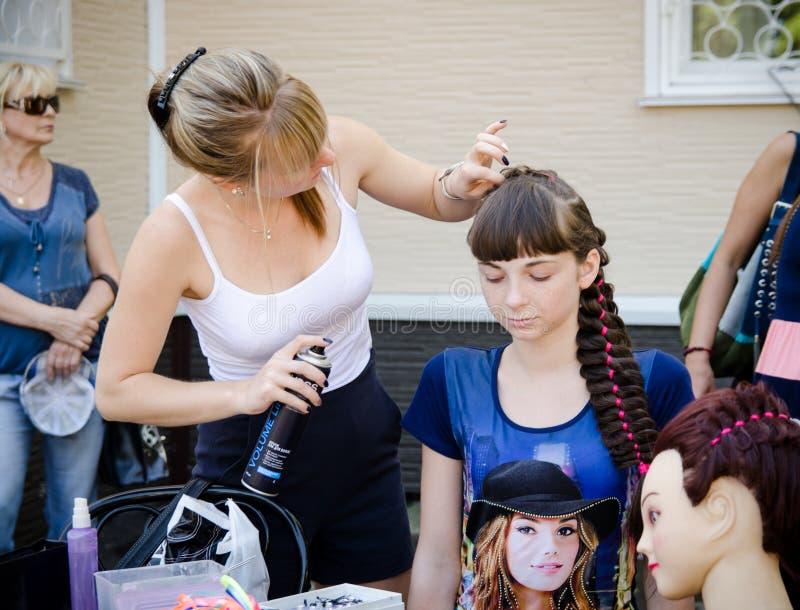 O cabeleireiro da mulher faz um penteado para uma menina em um partido da cidade foto de stock