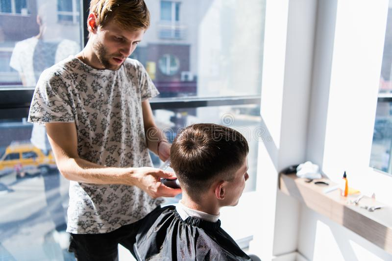 O cabeleireiro está nivelando um corte de cabelo com a ajuda de uma lâmina elétrica e de um pente em um barbeiro imagens de stock royalty free