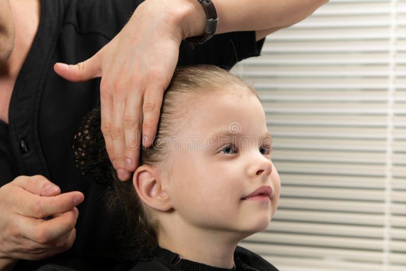 O cabeleireiro faz à menina um bolo do penteado imagens de stock royalty free