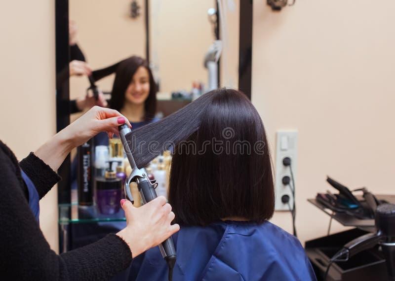 O cabeleireiro faz alinha o cabelo com o ferro a uma moça, morena do cabelo em um salão de beleza imagens de stock