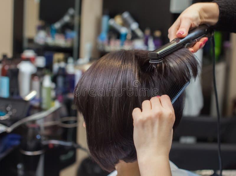 O cabeleireiro faz alinha o cabelo com o ferro a uma moça, morena do cabelo em um salão de beleza imagem de stock