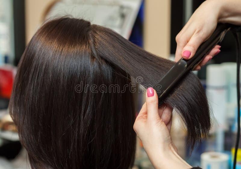 O cabeleireiro faz alinha o cabelo com o ferro a uma moça, morena do cabelo em um salão de beleza foto de stock