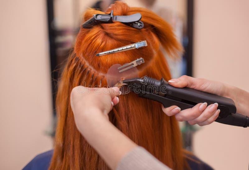O cabeleireiro faz extensões do cabelo a uma menina nova, ruivo imagens de stock royalty free