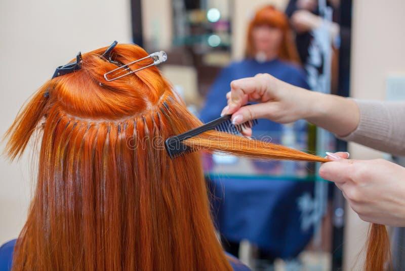 O cabeleireiro faz extensões do cabelo a uma menina nova, ruivo, em um salão de beleza fotografia de stock
