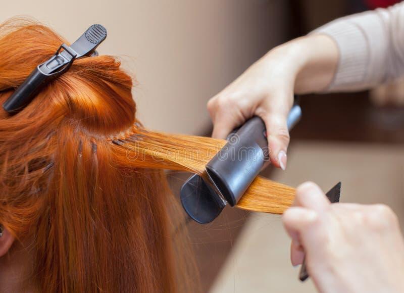 O cabeleireiro faz extensões do cabelo a uma moça, uma menina do ruivo em um salão de beleza imagem de stock royalty free
