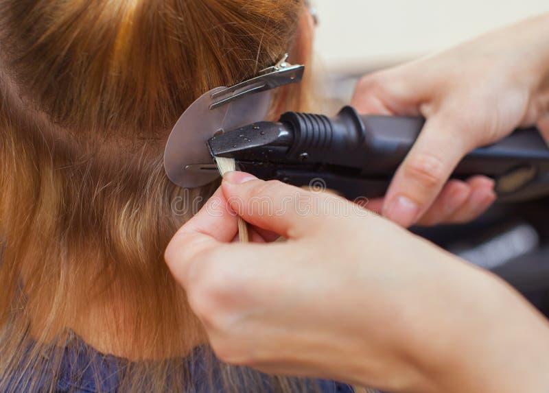 O cabeleireiro faz extensões do cabelo a uma moça, um louro em um salão de beleza foto de stock