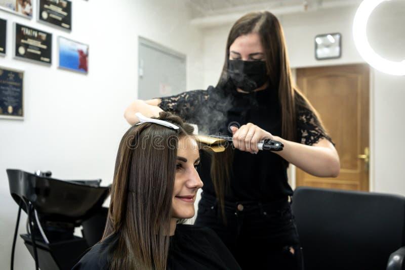 O cabeleireiro faz a laminação do cabelo em um salão de beleza para uma menina com cabelo moreno Conceito dos cuidados capilares fotos de stock royalty free