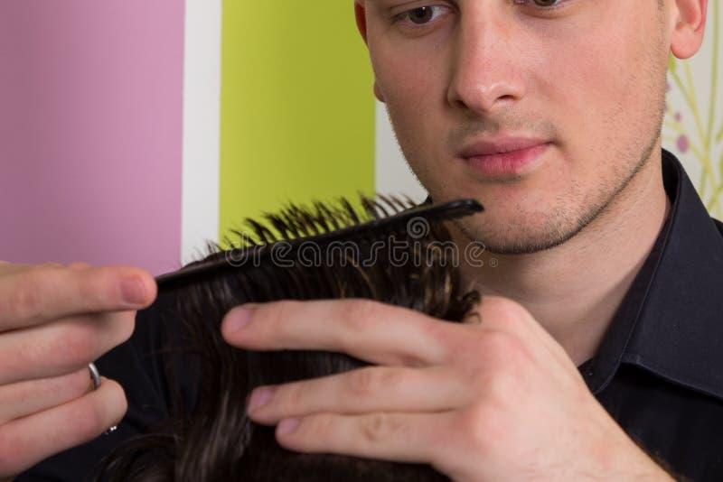 O cabeleireiro faz o cabelo com a escova do cliente no salão de beleza profissional do cabeleireiro imagem de stock