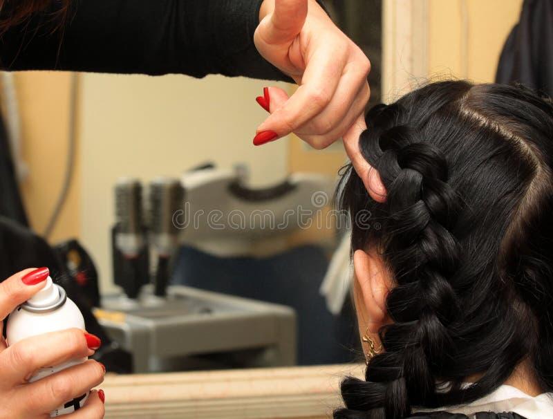 O cabeleireiro faz o penteado no cabelo preto longo fotografia de stock