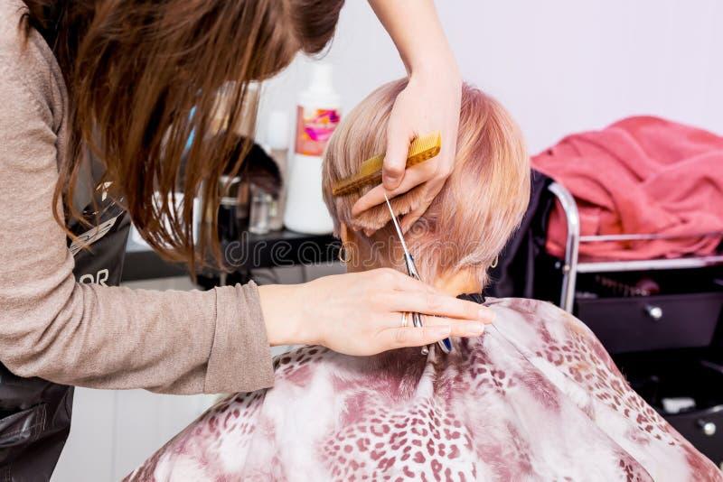 O cabeleireiro faz o penteado à moda para uma mulher idosa foto de stock