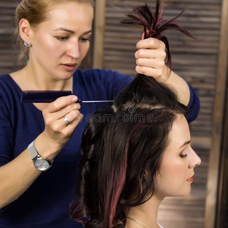O cabeleireiro faz o penteado para a mulher luxuoso corte de cabelo sob a forma da onda grande Penteado do casamento do conceito foto de stock