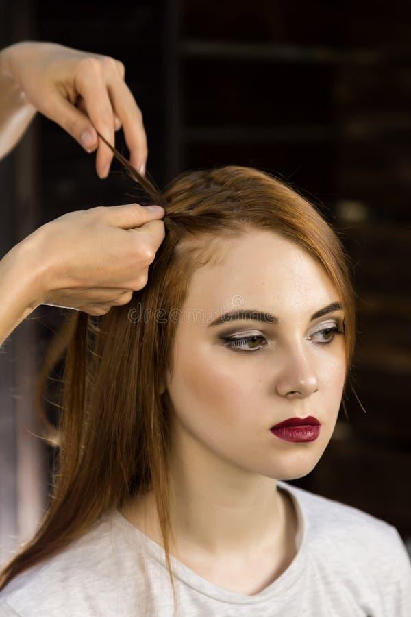 O cabeleireiro faz o penteado para que a jovem mulher teça tranças Beleza e casamento do conceito imagens de stock
