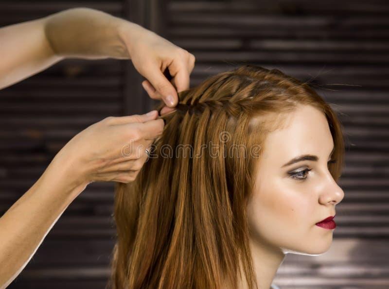 O cabeleireiro faz o penteado para que a jovem mulher teça tranças Beleza e casamento do conceito foto de stock royalty free