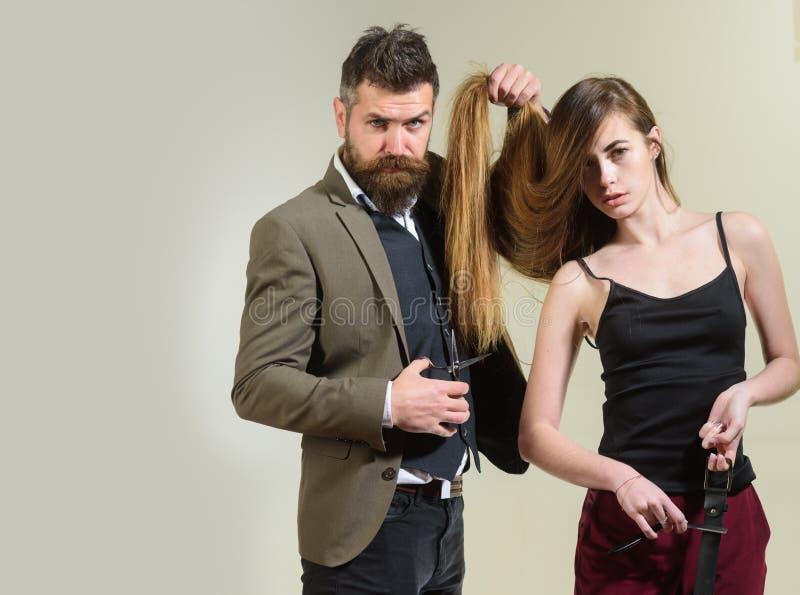 O cabeleireiro faz a penteado uma mulher com cabelo longo Cabeleireiro de visita da mulher Cuidados capilares fotografia de stock