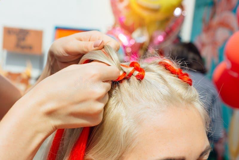 O cabeleireiro faz tranças com kanekalon vermelho fotos de stock