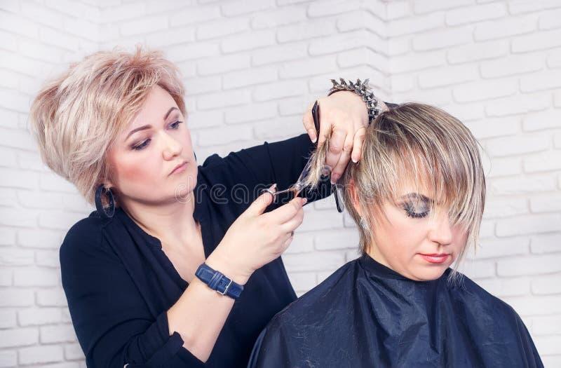 O cabeleireiro faz um cabelo cortar com tesouras fotografia de stock royalty free