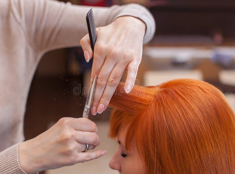 O cabeleireiro faz um corte de cabelo com as tesouras do cabelo a um jovem com a menina vermelha do cabelo fotografia de stock royalty free