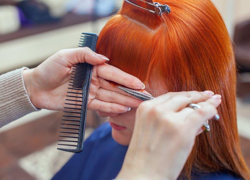 O cabeleireiro faz um corte de cabelo com as tesouras do cabelo a um jovem com a menina vermelha do cabelo fotografia de stock
