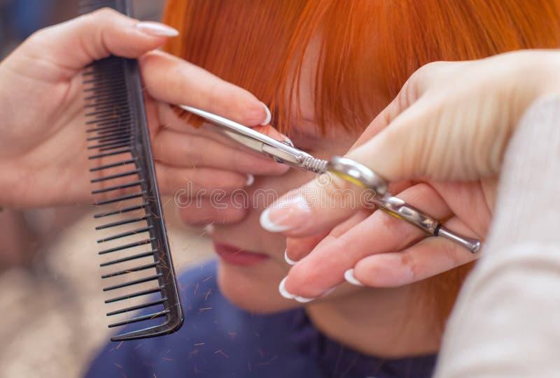 O cabeleireiro faz um corte de cabelo com as tesouras do cabelo a um jovem com a menina vermelha do cabelo imagens de stock