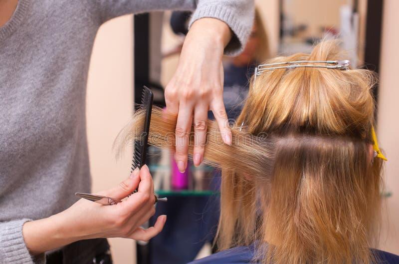 O cabeleireiro faz um corte de cabelo com as tesouras do cabelo a uma moça, um louro fotos de stock royalty free