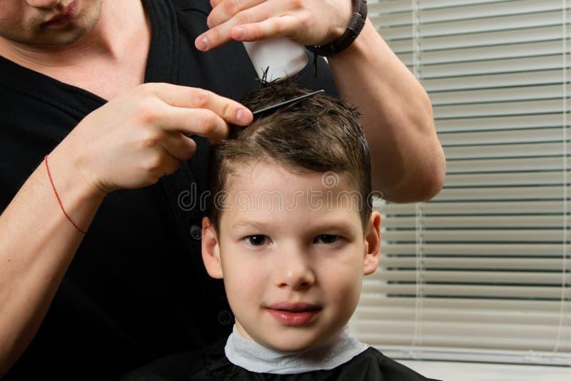 O cabeleireiro faz um corte de cabelo para o menino e aplica um remédio para o penteado fácil imagem de stock royalty free