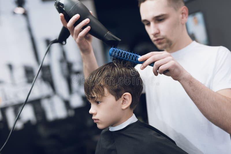 O cabeleireiro faz um penteado bonito elegante para o menino em um barbeiro moderno foto de stock