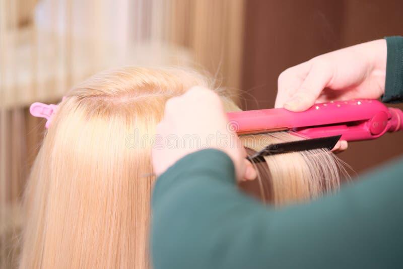 O cabeleireiro faz a um penteado a menina loura em um sal?o de beleza com ferro de ondula? imagem de stock