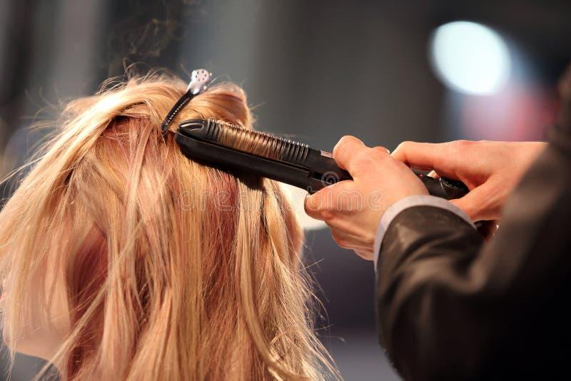 O cabeleireiro gerencie o ferro de ondulação do cabelo da moça foto de stock