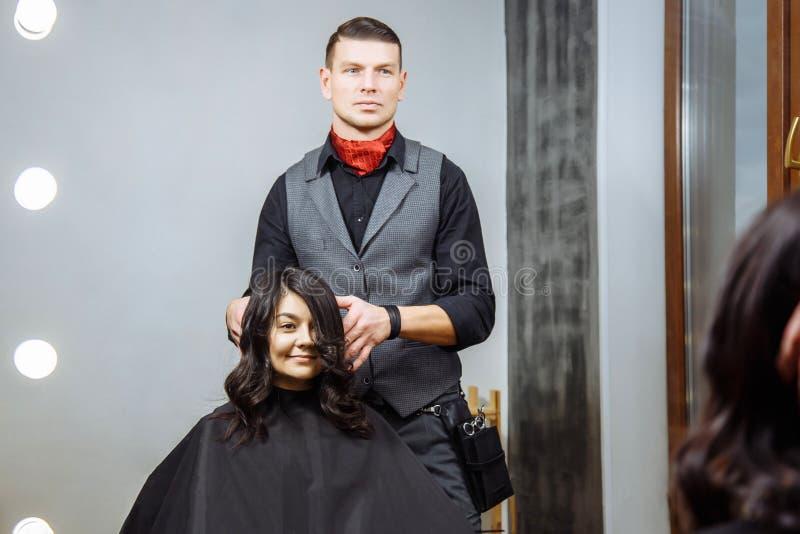 O cabeleireiro masculino bonito faz o cabelo que denomina uma jovem mulher em um salão de beleza imagem de stock