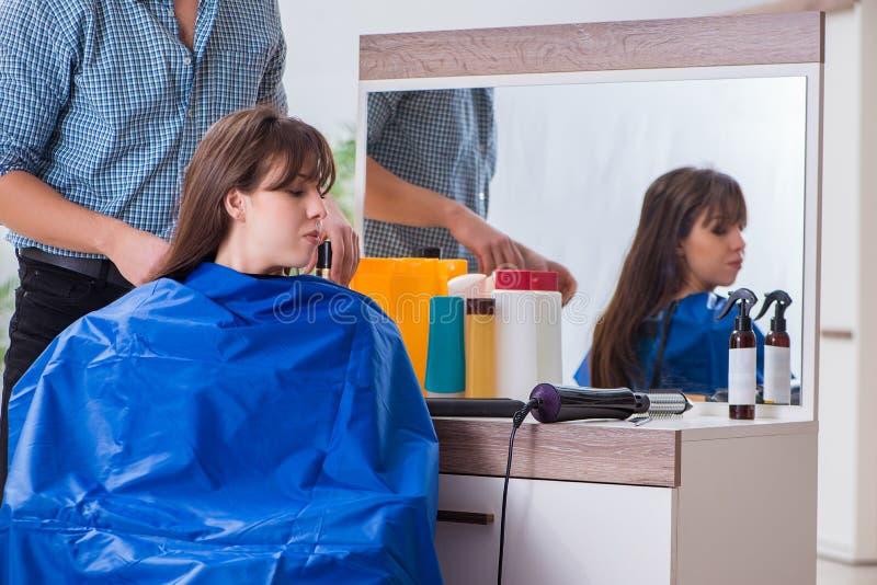 O cabeleireiro masculino do homem que faz o corte de cabelo para a mulher fotos de stock royalty free