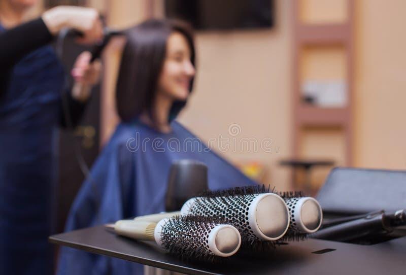 O cabeleireiro seca seu cabelo uma menina moreno em um salão de beleza foto de stock