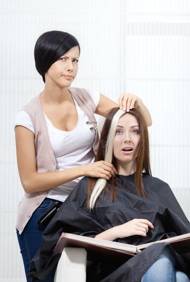 O cabeleireiro tenta o fechamento do cabelo tingido na mulher foto de stock royalty free
