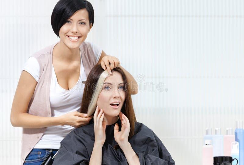 O cabeleireiro tenta o fechamento do cabelo tingido no cliente foto de stock