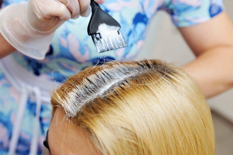 O cabeleireiro usa uma escova para aplicar a tintura ao cabelo, para d fotografia de stock