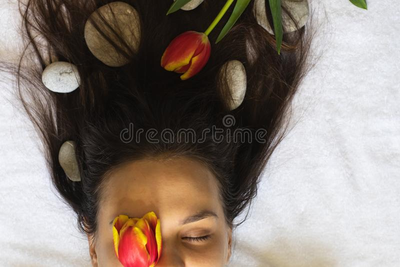 O cabelo da moça torcido com pedras e tulipas dos termas foto de stock royalty free