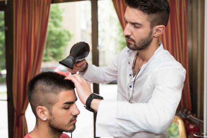 O cabelo de Blow Dry Man do cabeleireiro na loja fotos de stock