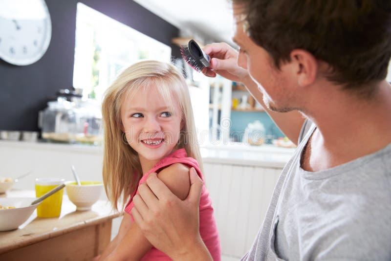 O cabelo de Brushing Daughter do pai na tabela de café da manhã imagem de stock royalty free