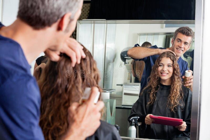 O cabelo de Setting Client do cabeleireiro ao olhar imagem de stock