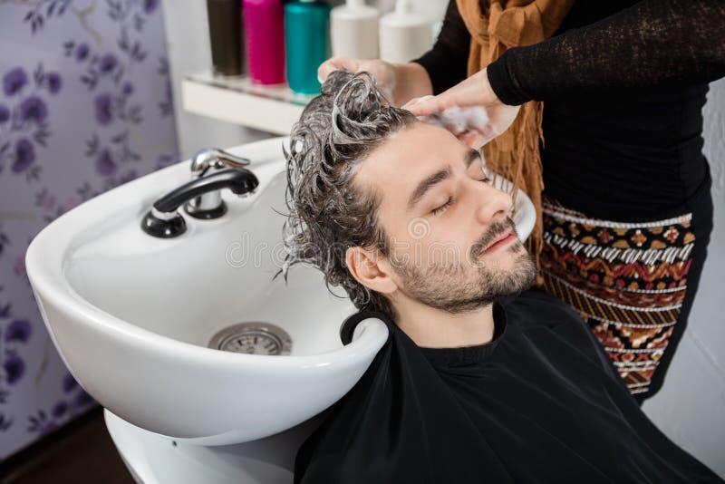 O cabelo de Washing Male Client do esteticista no salão de beleza fotografia de stock
