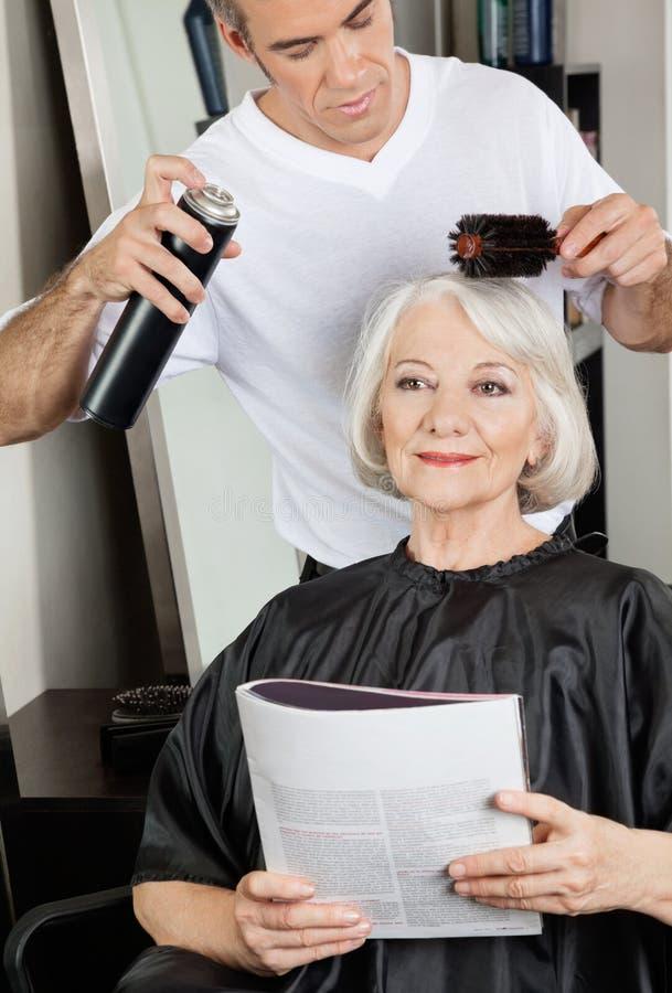 O cabelo do cliente da fundação do barbeiro no salão de beleza imagens de stock royalty free