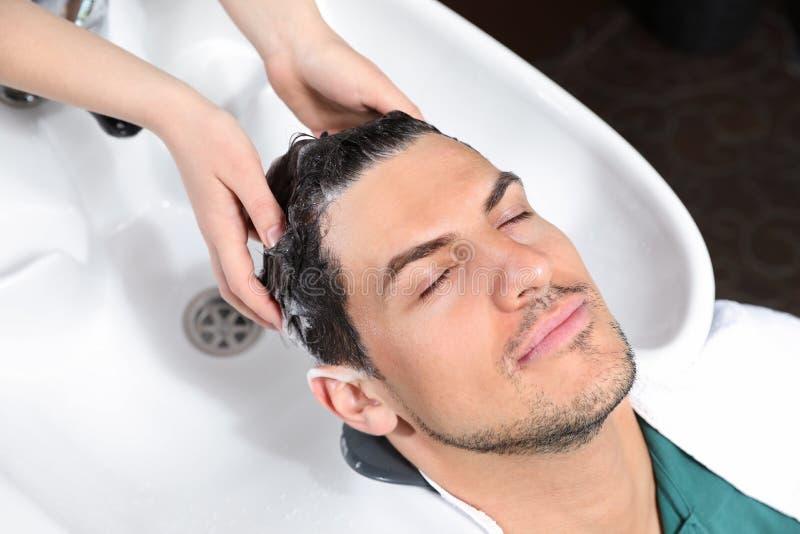O cabelo do cliente da lavagem do estilista no dissipador imagens de stock