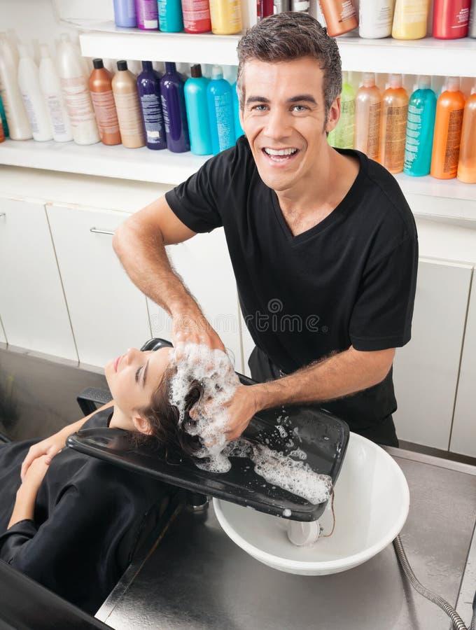 O cabelo do cliente de lavagem do barbeiro imagem de stock royalty free