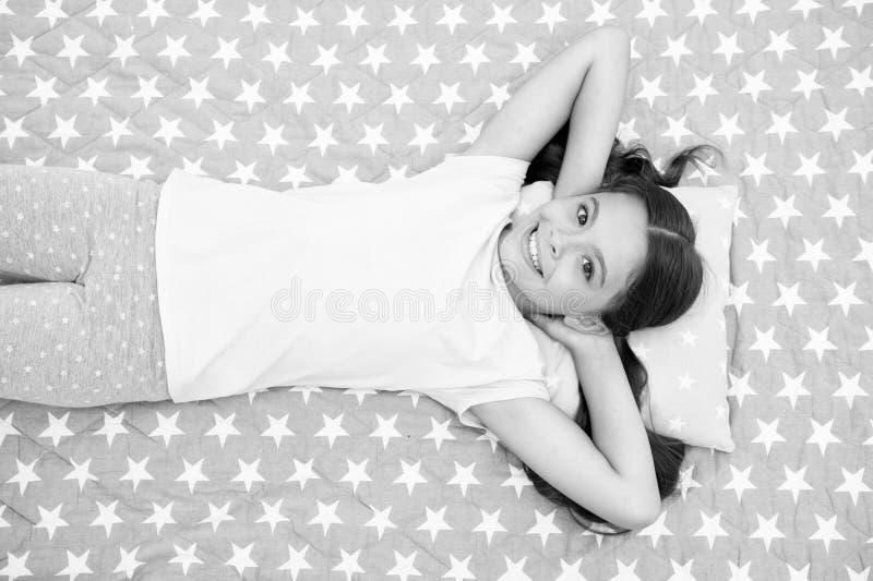 O cabelo longo da criança da menina coloca a vista superior acordada A qualidade do sono depende de muitos fatores A menina coloc fotos de stock